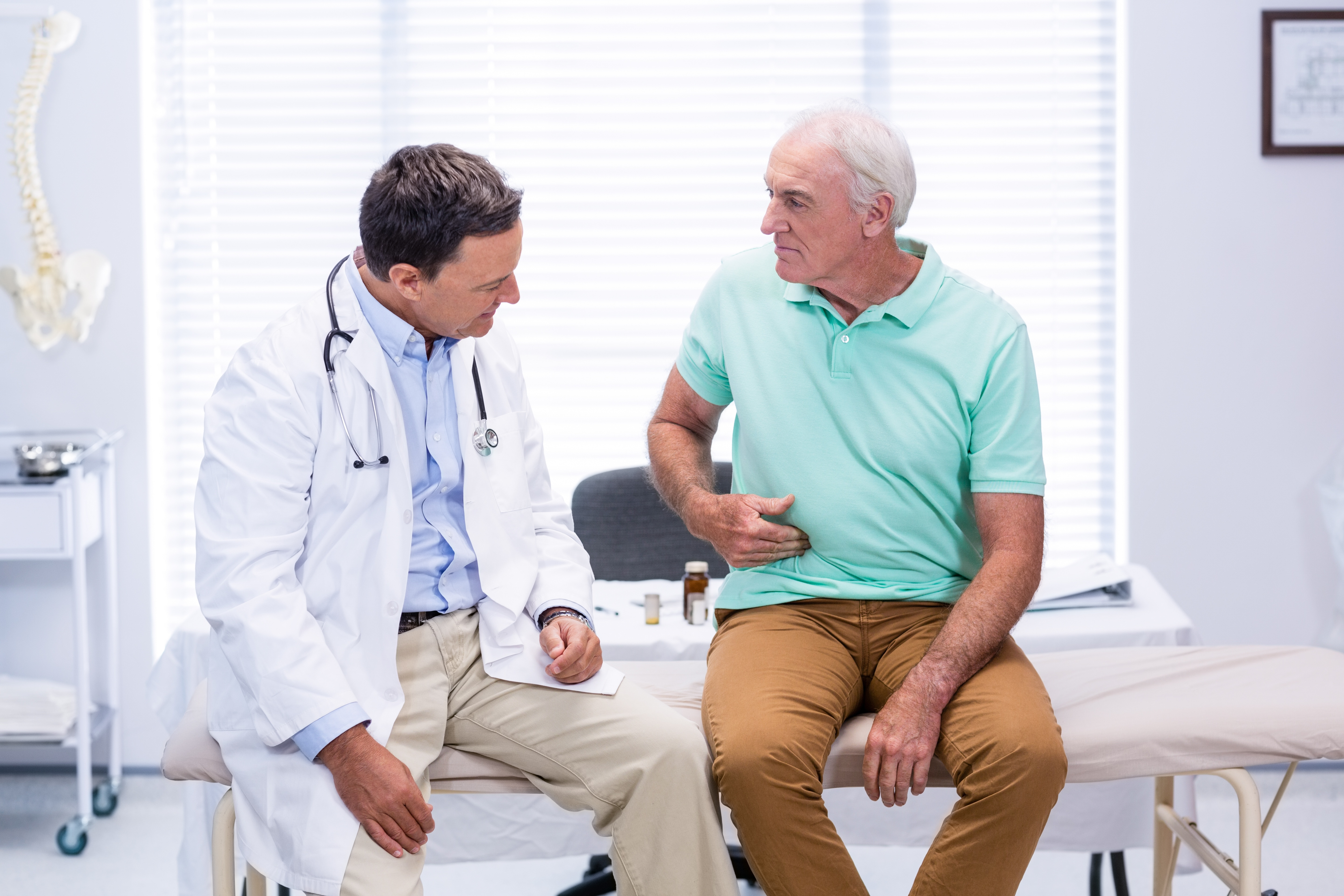 senior man showing stomach ache pain to gastroenterologist